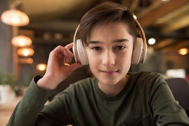 Kleine jongen studeert door groepsvideogesprek, gebruik videoconferentie met leraar, luisterend naar online cursus.