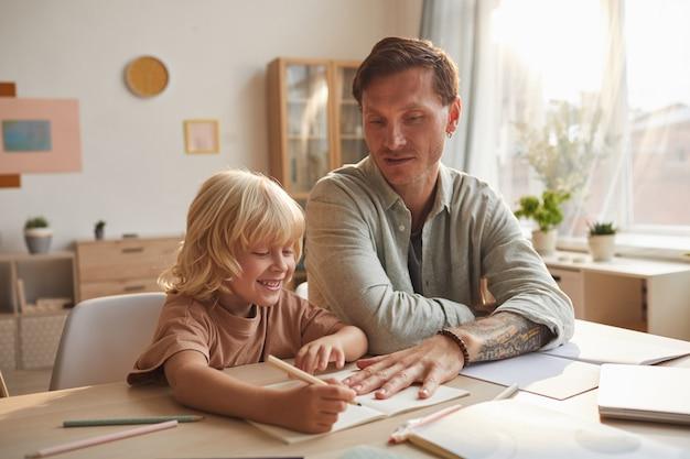 Kleine jongen studeert met zijn vader aan de tafel, zijn vader helpt hem met huiswerk in de kamer