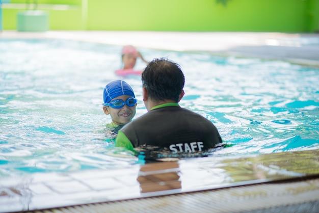 Kleine jongen studeren in zwemles met docenten