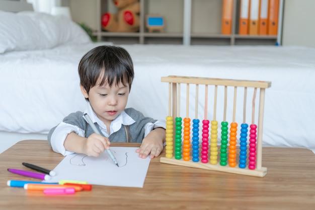 Kleine jongen tekenen in het witboek met genieten