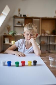 Kleine jongen tekenen met gouache, kinderen in workshop