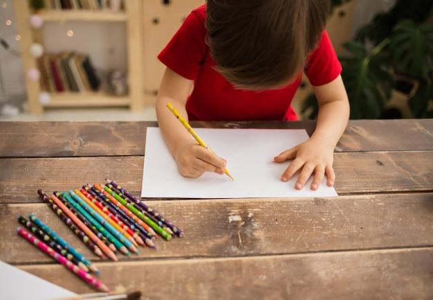 Kleine jongen tekent met een kleurpotlood op wit papier aan een houten tafel in de kamer