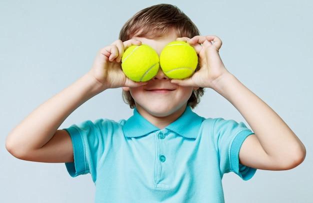 Kleine jongen tennisballen houden in plaats van de ogen en glimlachen
