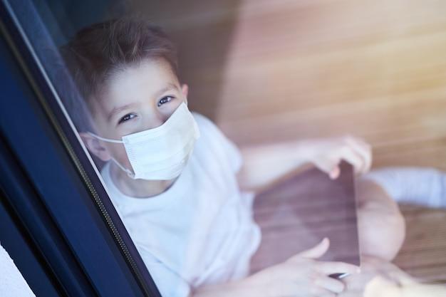 Kleine jongen thuis in quarantaine tijdens de pandemie van het coronavirus