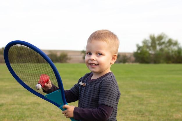 Kleine jongen tijdens tennistraining of training. peuter die badminton speelt in het zomerpark. kind met kleine tennisracket en bal. kid tennisser