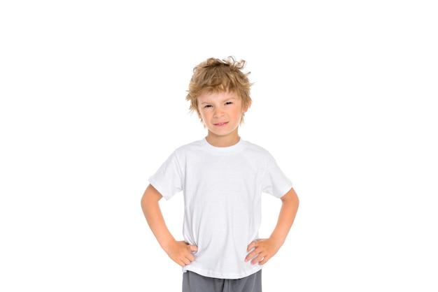Kleine jongen toont zijn ongenoegen over zijn gezichtsuitdrukking en houdt zijn handen op zijn middel.