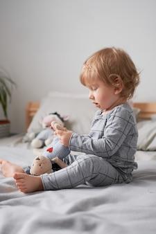 Kleine jongen van een jaar spelen op het bed met zijn favoriete speelgoed lifestyle foto
