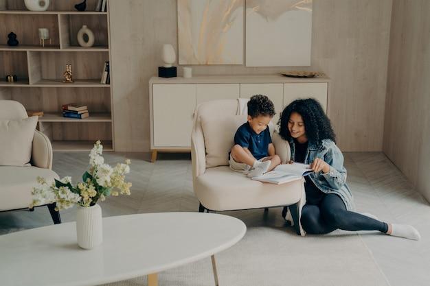 Kleine jongen van gemengd ras leest met zijn liefhebbende moeder terwijl hij geniet van de tijd samen in de woonkamer thuis