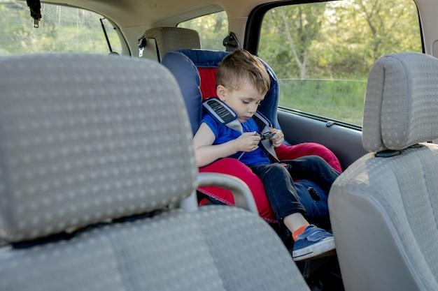 Kleine jongen vastgemaakt met veiligheidsgordel in de auto. voertuig- en transportconcept.