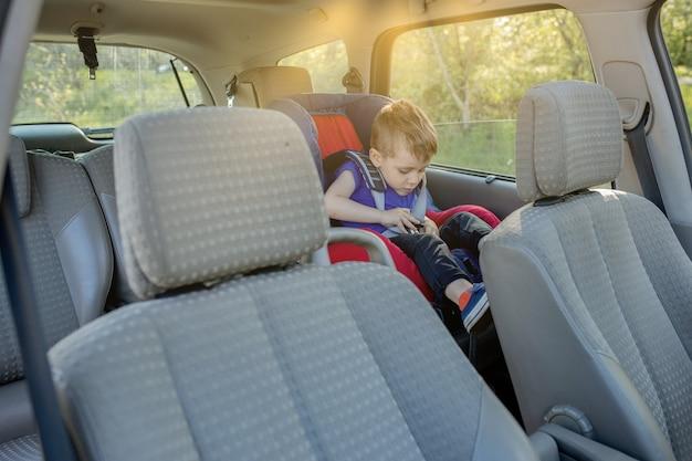 Kleine jongen vastgemaakt met veiligheidsgordel in de auto. voertuig- en transportconcept