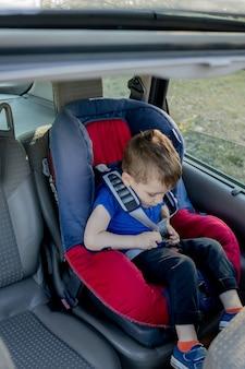 Kleine jongen vastgemaakt met veiligheidsgordel in de auto