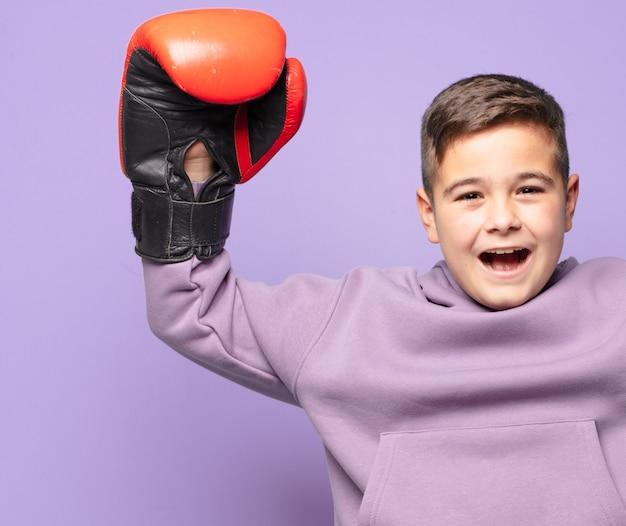 Kleine jongen viert succesvol een overwinning. boks concept