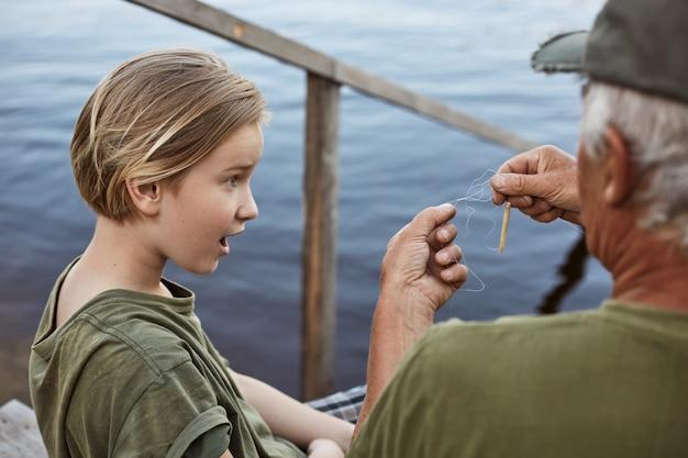 Kleine jongen vissen met zijn vader, verbaasd vanwege verwarde lijn op hengel, familie poseren op houten trap naar water, verrast mannelijk kind.