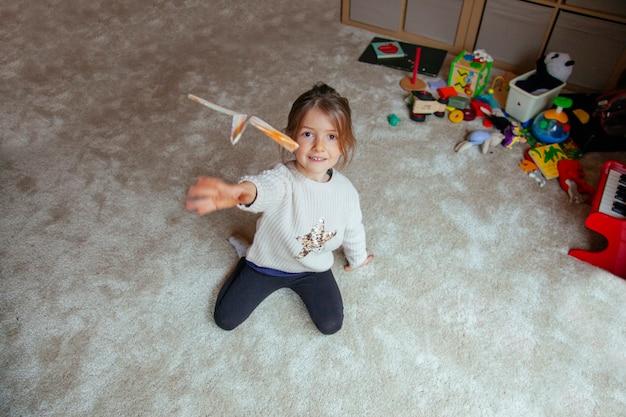 Kleine jongen vliegen een origami papieren vliegtuigje