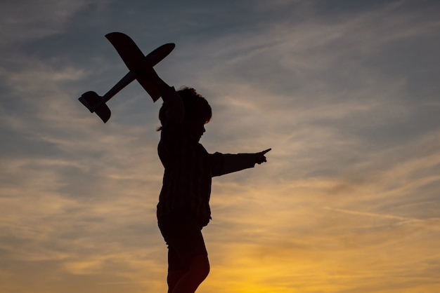 Kleine jongen vlieger over avondrood. de jongen droomt ervan piloot te worden. leuk kind dat in de tarwe loopt
