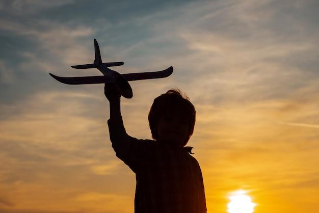 Kleine jongen vlieger over zonsondergang. mijn lieve kinderen met speelgoedvliegtuig in een veld bij zonsondergang. succes en