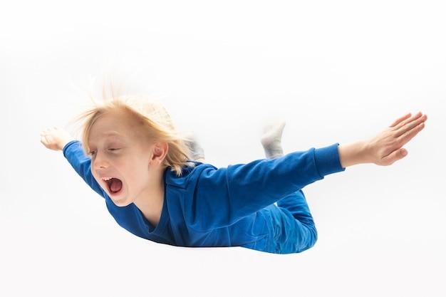 Kleine jongen vliegt, valt of zweeft in de lucht. vliegen in droom, dromen.
