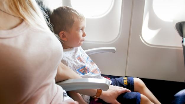 Kleine jongen voelt zich bang voor de eerste vlucht in het vliegtuig.