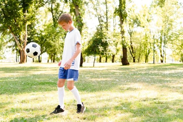 Kleine jongen voetballen met kopie ruimte