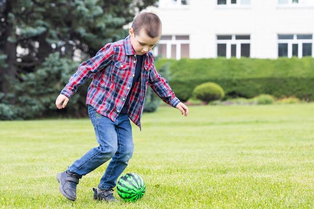 Kleine jongen voetballen met voetbal op veld in zomer park.
