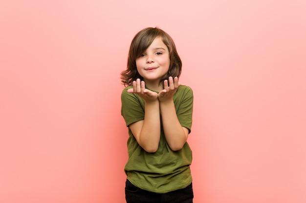 Kleine jongen vouwen lippen en handpalmen om lucht kus te sturen.