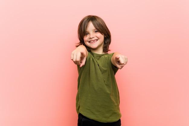 Kleine jongen vrolijke glimlach wijzend naar de voorkant.