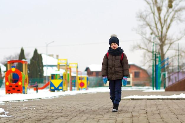 Kleine jongen wandelen in het park. kind gaat na school wandelen met een schooltas in de winter. kinderen activiteit buiten in de frisse lucht. gezonde manier van leven concept.