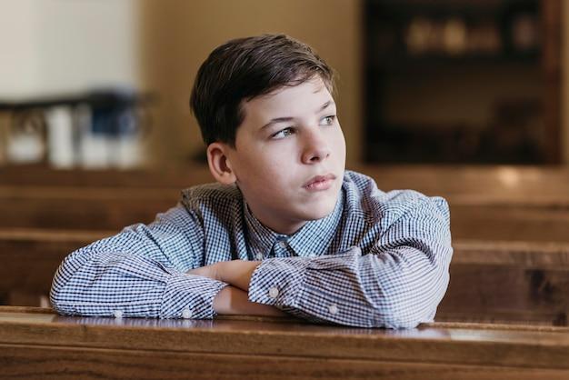 Kleine jongen wegkijken in de kerk