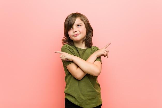 Kleine jongen wijst zijwaarts, probeert te kiezen tussen twee opties.