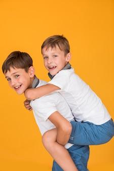 Kleine jongen wordt door zijn broer gedragen