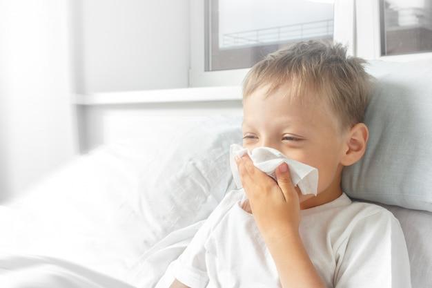 Kleine jongen ziek in bed met temperatuur. het kind werd verkouden. hij niest, hoest en heeft een loopneus. gezondheidszorg, griep, hygiëne.