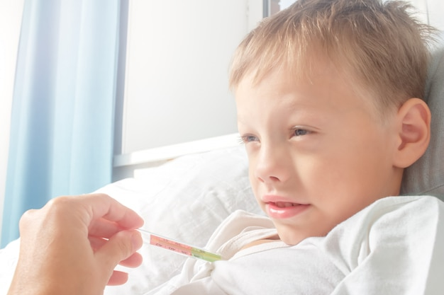 Kleine jongen ziek in bed met temperatuur, terwijl zijn moeder zijn temperatuur neemt. het kind werd verkouden. gezondheidszorg, griep, hygiëne.