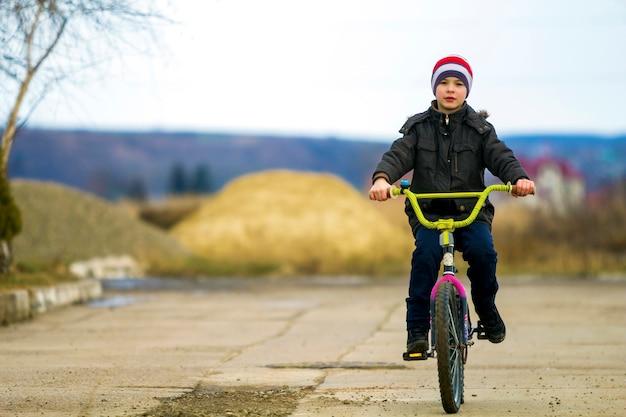 Kleine jongen zijn fiets in park buiten.
