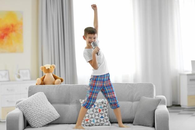 Kleine jongen zingen met een microfoon op een sofa thuis