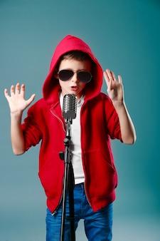 Kleine jongen zingen met microfoon op een grijze ondergrond
