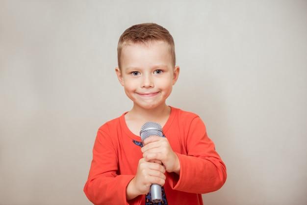 Kleine jongen zingen met microfoon op grijze achtergrond. muziek, zang en onderwijsconcept