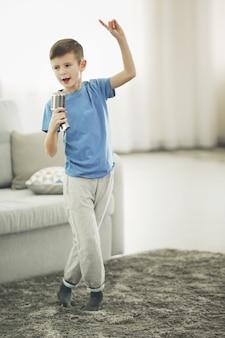 Kleine jongen zingen met microfoon thuis
