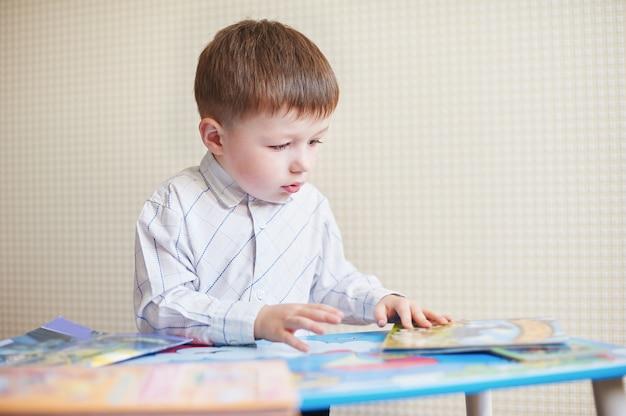 Kleine jongen zit aan het bureau en leest boek.