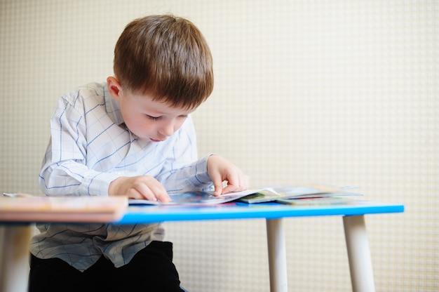 Kleine jongen zit aan zijn bureau en leest een boek.