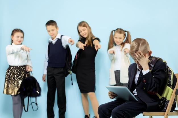 Kleine jongen zit alleen op een stoel en lijdt aan pesterijen terwijl kinderen spotten. triest jonge schooljongen zittend op studio tegen blauwe achtergrond.