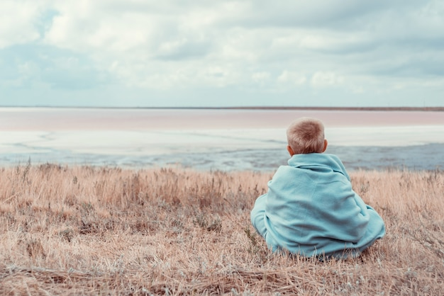 Kleine jongen zit in de buurt van de zee wreapped in warme deken