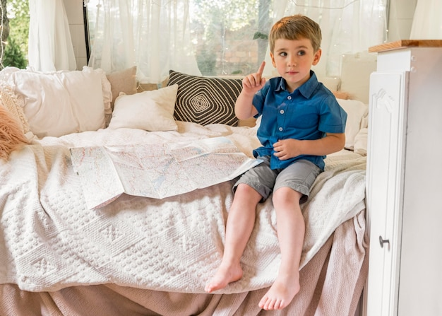 Kleine jongen zit in een caravan naast een kaart