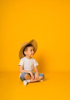 Kleine jongen zit in een t-shirt en korte broek met een strooien hoed en kijkt weg op een geel oppervlak