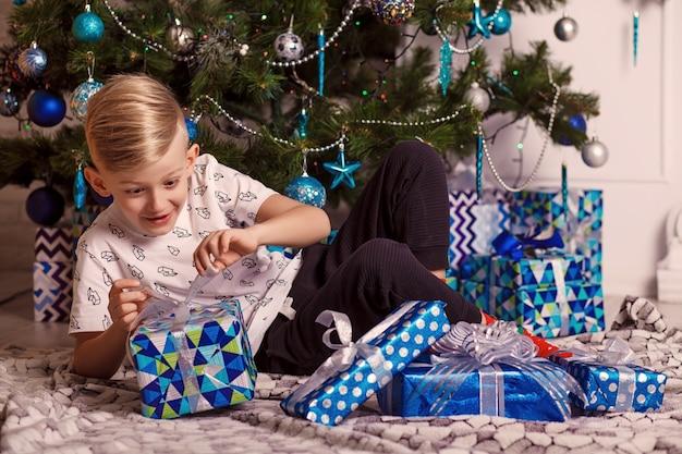 Kleine jongen zit met een geschenk in de buurt van de kerstboom.