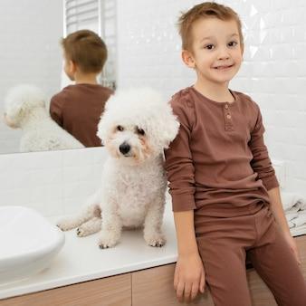 Kleine jongen zit naast zijn hond in de badkamer