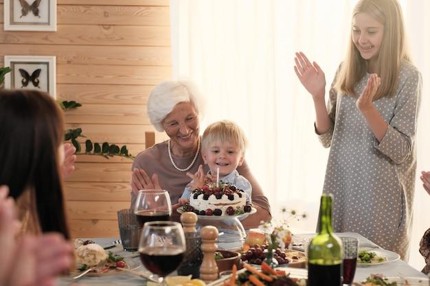 Kleine jongen zit op de knieën van zijn grootmoeder en blaast kaars op de taart terwijl zijn familie hem feliciteert met zijn verjaardag