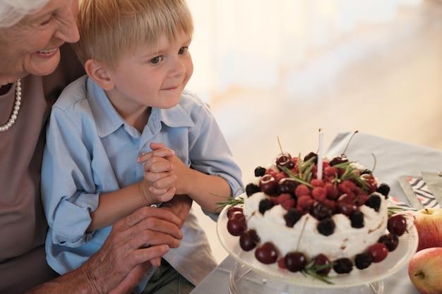 Kleine jongen zit op de knieën van zijn grootmoeder en blaast kaars op zijn verjaardagstaart