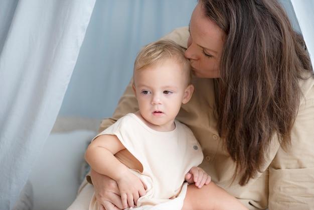 Kleine jongen zit op de schoot van zijn moeder