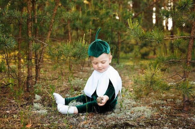 Kleine jongen zit op een bospad in een sneeuwklokje kostuum. jongens gekleed in een grappig sneeuwklokje kostuum met een hoed Premium Foto