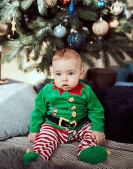 Kleine jongen zit op een kerstboom